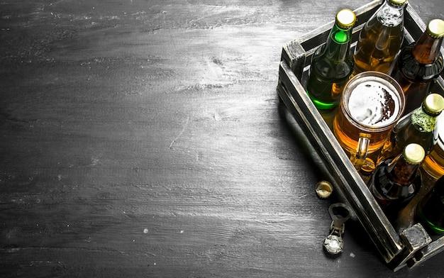 Свежее пиво в старой коробке на черной доске