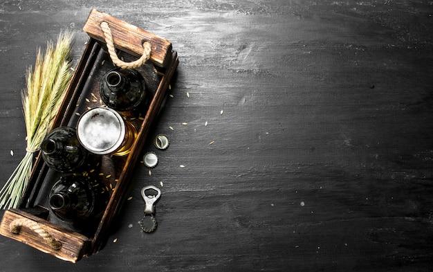 Свежее пиво в очках и в старой коробке. на черной доске.