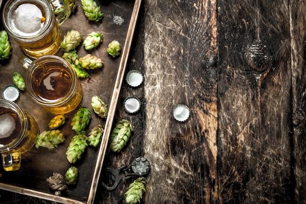 Свежее пиво в очках с зеленым хмелем на старом подносе. на деревянном столе.