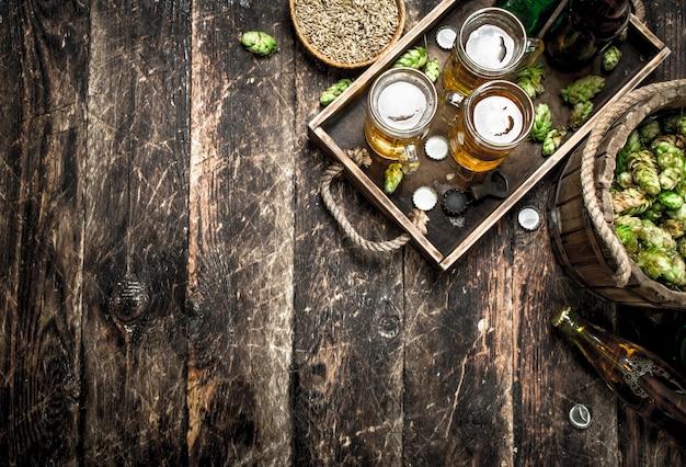 Свежее пиво в очках с зелеными хмелями на старом подносе на деревянном столе.