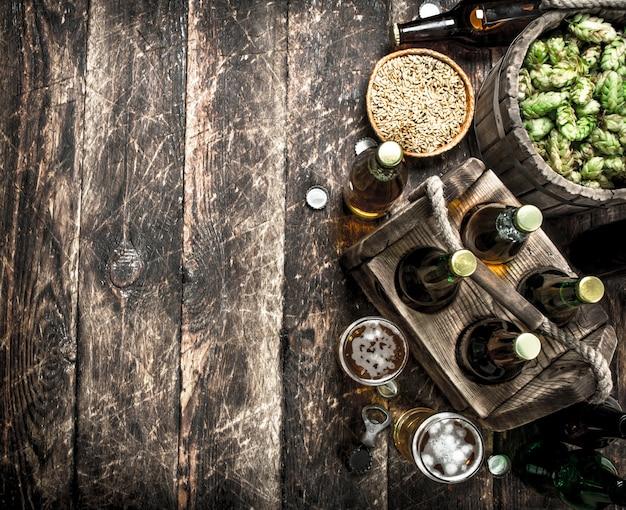 녹색 홉과 맥아를 곁들인 신선한 맥주. 나무 배경.