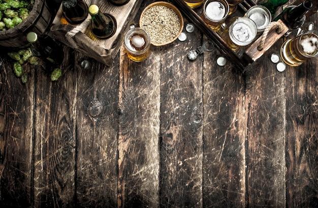 Свежее пиво с зеленым хмелем и солодом. на деревянном столе.