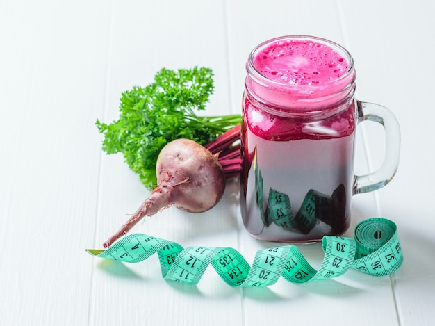 Fresh beetroot smoothie, measuting tape and parsley on white wooden table
