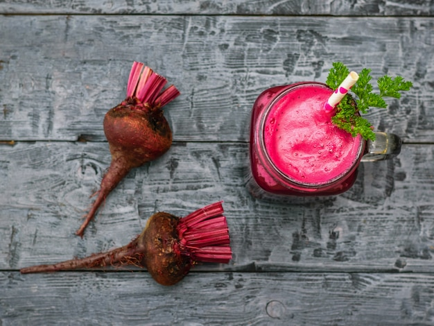 Fresh beetroot smoothie and two beet on black rustic table