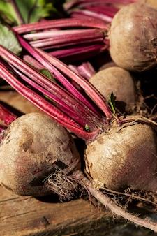 나무 테이블에 상판이 있는 신선한 사탕무. 자연에서 온 비타민과 건강. 확대. 수직의.