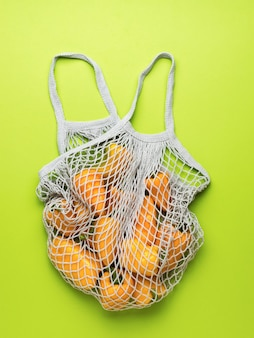 Fresh bell pepper in a mesh bag on a green background. vegetarian food. a fresh crop of vegetables.