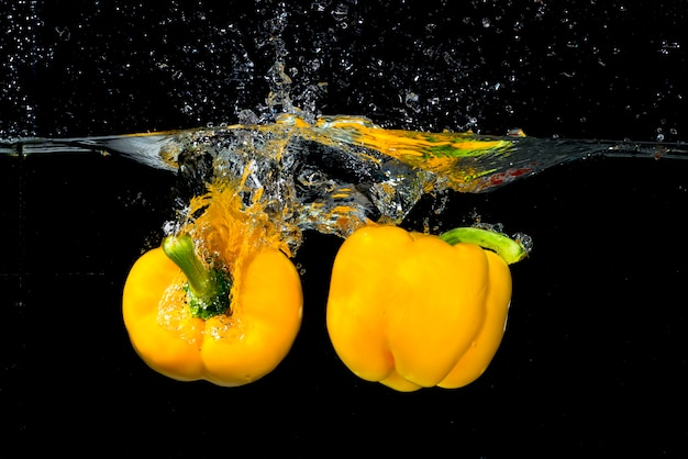 Fresh bell peppers falling in water against black background