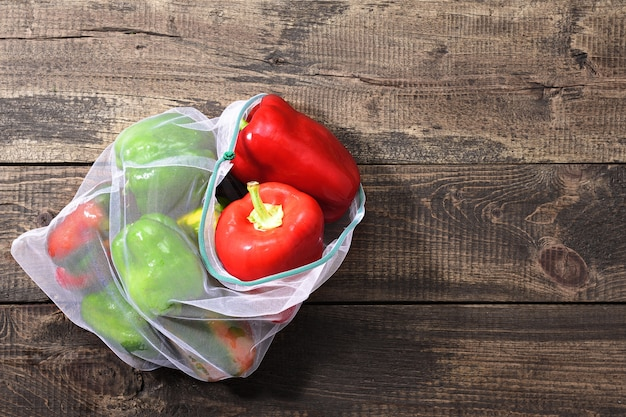 Fresh bell peppers in reusable eco-friendly pouch on wooden background with copy space.