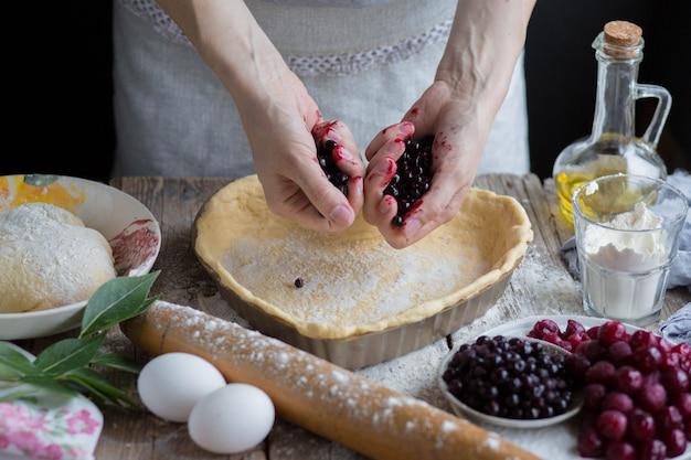Свежие ягоды льются из рук девушки. домашняя выпечка.