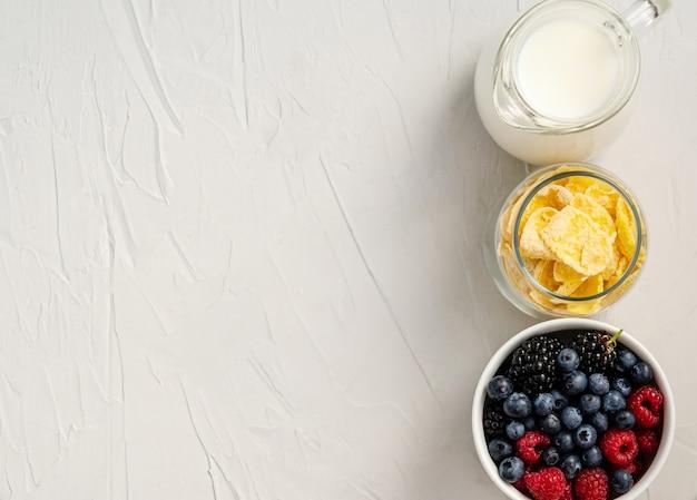 신선한 딸기, 콘플레이크, 우유-흰색 배경에 간식이나 아침 식사 재료. 평평하다, 복사 공간, 텍스트를위한 공간. 위에서 봅니다.