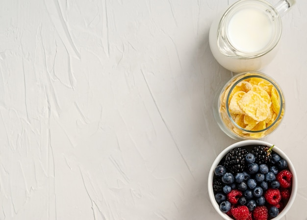 Fresh berries, cornflakes, milk - ingredients for a snack or breakfast on a white background. flat lay, copy space, space for text. view from above.