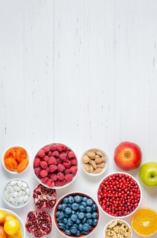 白い木製の背景に新鮮なベリー、フルーツ、ナッツ。健康的な食事の概念。食品にはビタミンと微量元素が含まれています。スペースをコピーします。