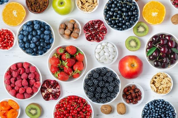 신선한 딸기, 과일, 견과류는 흰색 나무 바탕에. 건강한 식습관의 개념. 음식에는 비타민과 미량 원소가 포함되어 있습니다.