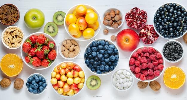 白い木製の背景に新鮮なベリー、フルーツ、ナッツ。健康的な食事の概念。食品にはビタミンと微量元素が含まれています