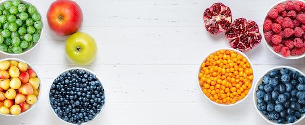 白い木製の背景に新鮮なベリーフルーツナッツ健康的な食事の概念