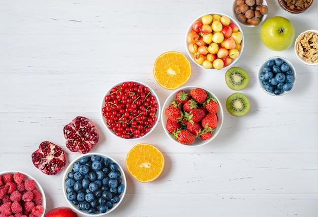 白い木製の背景に新鮮なベリー、フルーツ、ナッツ。健康的な食事の概念
