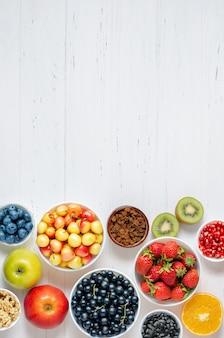 白い木製の背景に新鮮なベリー、フルーツ、ナッツ。