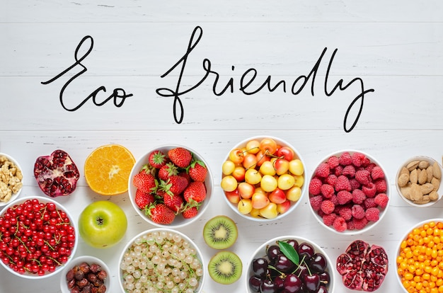 Fresh berries, fruits, nuts on a white wooden background. t