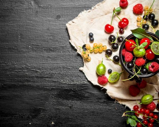 Свежие ягоды в чашке на старой ткани. на черном деревянном столе.