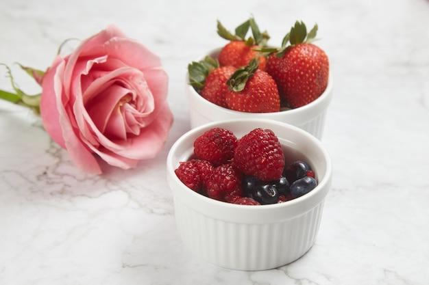 Свежие ягоды в мисках и роза на белом мраморном фоне.