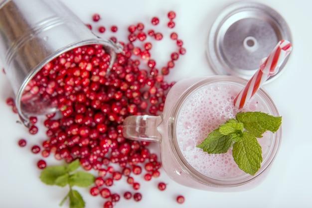 白いテーブルの上でカウベリーとベリーの新鮮なベリーが揺れます。スムージーの健康的な食事の概念