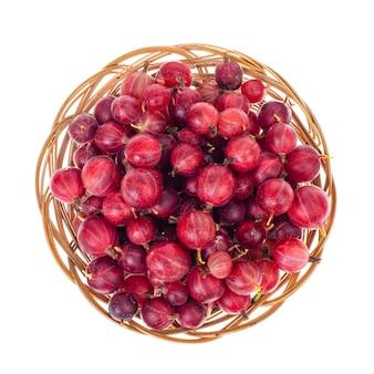 白い背景の上のボウルに赤いグーズベリーの新鮮なベリー。