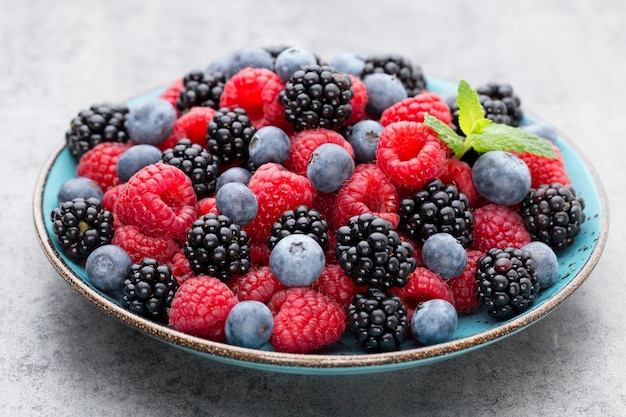 Fresh berries in a plate on a  wooden background