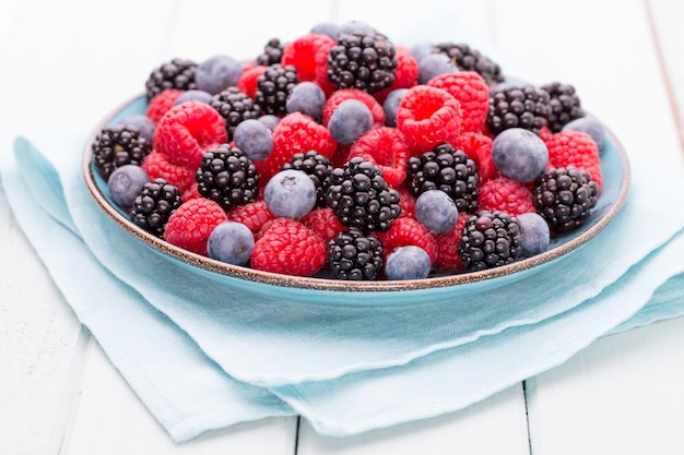 Fresh berries in a plate on a  wooden surface. flat lay, top view, copy space.