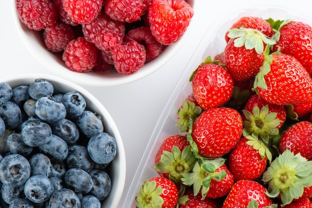 Свежие ягоды малины, клубники и черники в мисках, изолированные на белом фоне, вид сверху