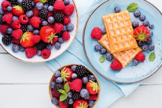 Салат из свежих ягод в тарелке на деревянном фоне. плоская планировка, вид сверху, копия пространства.