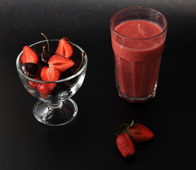 Свежие ягоды - клубника и вишня на черном