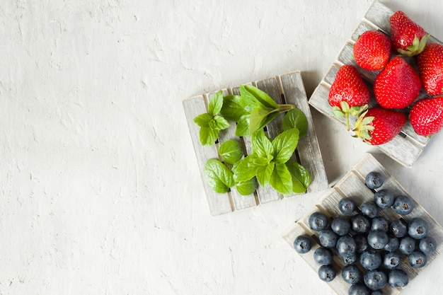 Fresh berries strawberries blueberries mint on a wooden stand, grey background with copy space for text