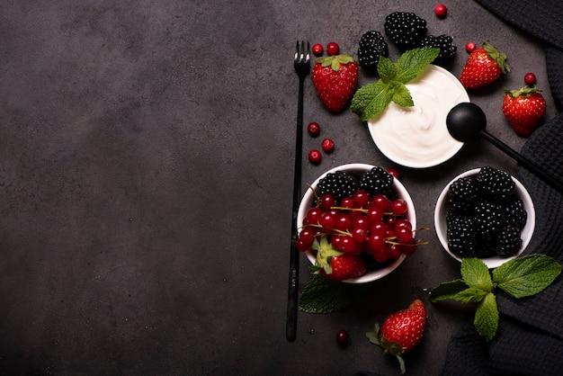 Свежие ягоды с мятой и домашней сметаной на черном столе