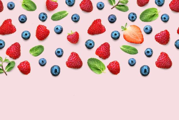 잘 익은 딸기와 민트의 신선한 베리와 과일 믹스 테두리 프레임 배너 분홍색 배경에 나뭇잎. 평평하다. 과일 패턴
