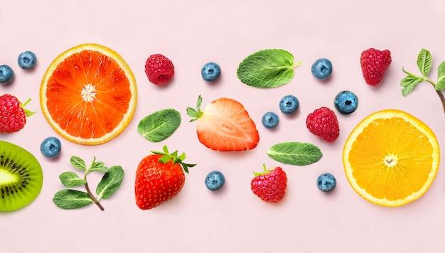 다양 한 익은 딸기와 민트의 신선한 베리와 과일 믹스 테두리 프레임 배너 분홍색 배경에 나뭇잎. 평평하다. 과일 패턴