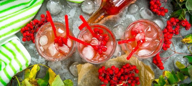 フレッシュベリーカクテル。氷と3つのカクテル。材料-石のテーブルの上の酒、ベリー、ジュース、そしてきれいな水。上面図