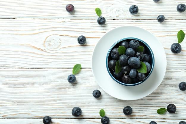 白い木製のテーブルにブルーベリーと新鮮なベリーのコンセプト