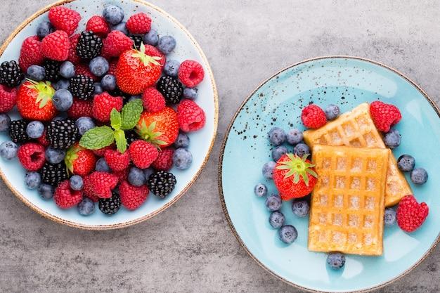 青い皿に新鮮なベリーのサラダ。ヴィンテージの木製の背景。