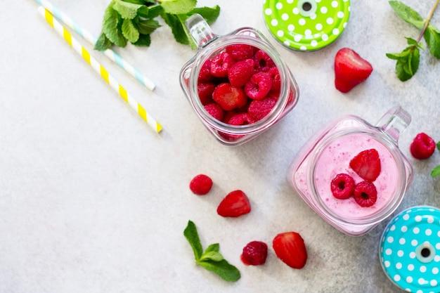 灰色の石またはスレート上の新鮮なベリーのスムージーと新鮮なイチゴとラズベリー