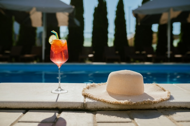 Fresh beverage in glass and hat at the edge of the pool, nobody. carefree summer vacation concept, holiday party at the poolside outdoors