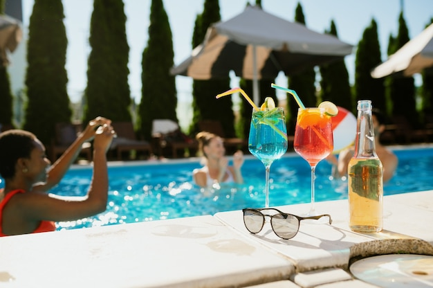 Fresh beverages in glasses at the edge of the pool