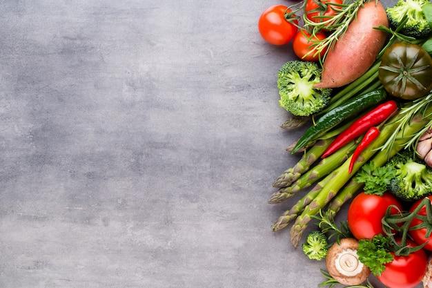 Свежие био овощи на серой каменной поверхности.