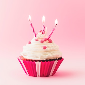 Fresh birthday cupcake with burning candles on pink backdrop