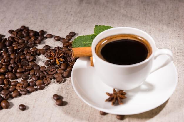 スターアニスとナチュラルトーンのキャンバス上のルーズビーンズによる白いプレート上のマグカップの新鮮なブラックコーヒー