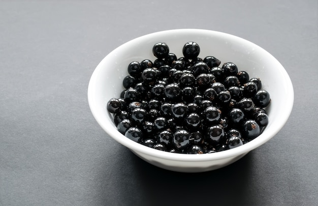 Fresh black currant on a snow-white plate, which stands on a black table. side view