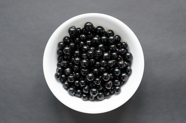 Fresh black currant on a snow-white plate, which stands on a black table. view from above