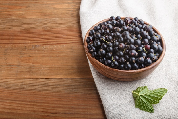 Fresh black currant in wooden bowl on wooden background. top view.