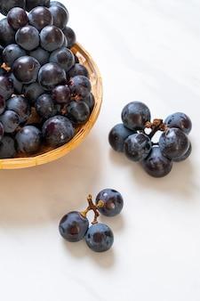 白いテーブルの上の新鮮な黒ブドウ