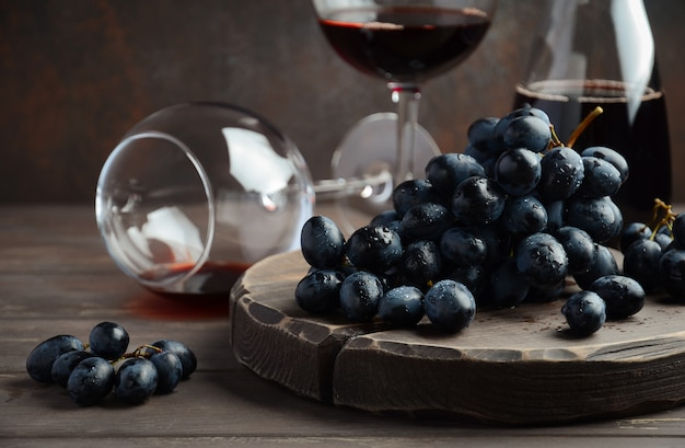 Fresh black grapes and red wine on wooden table