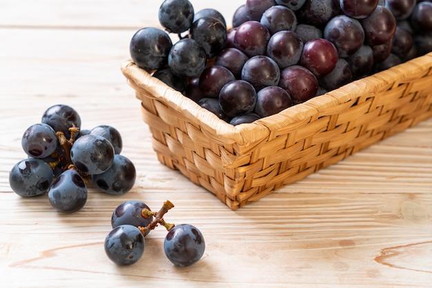 Fresh black grapes on white background